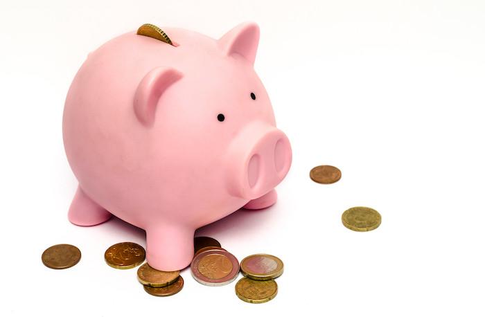 Piggybank with a few coins around it